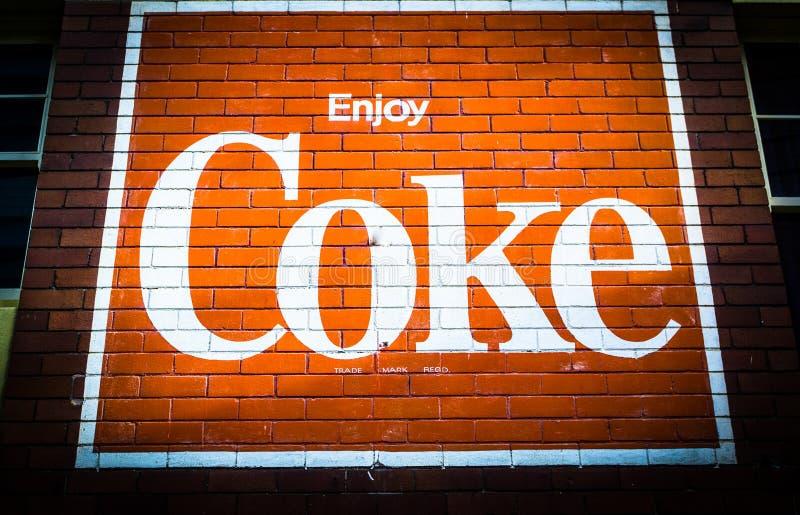 Logotipo da marca registrada clássica do casco ou da coca-cola na parede de tijolos vermelhos foto de stock royalty free