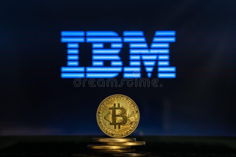 Logotipo de IBM en una pantalla de ordenador con una pila de monedas del cryptocurency de Bitcoin foto de archivo