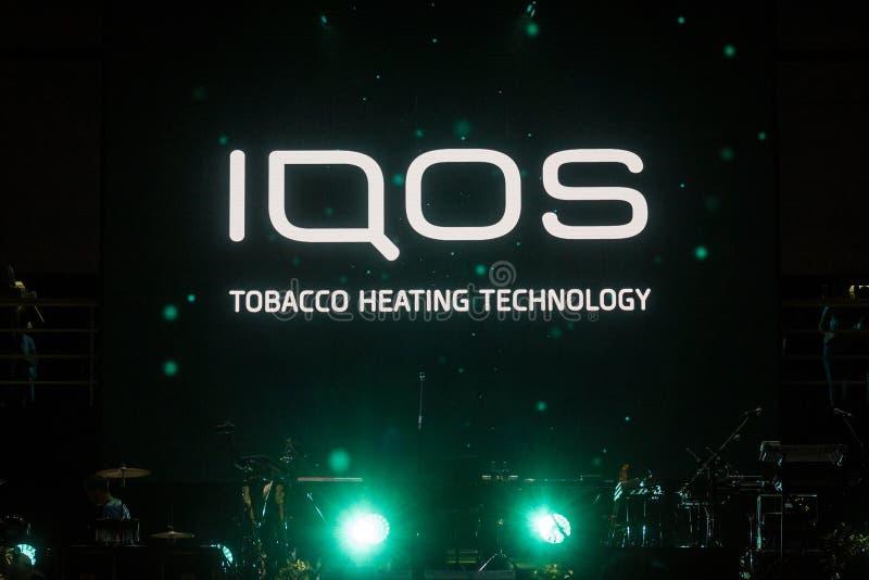 Logotipo de Iqos delante de la terraza de la barra en Serbia Iqos, beloning a Philip Morris International, es un sistema del ciga fotografía de archivo