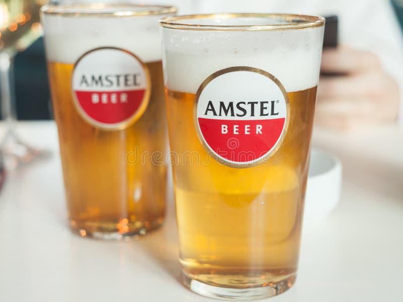 Logotipo de la cerveza de Amstel sobre un vidrio patrocinado por la marca Amstel es una cerveza ligera holandesa de pilsner produ fotografía de archivo