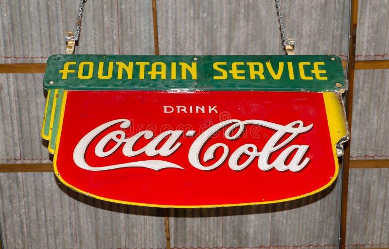 Logotipo de marcado en caliente de la marca registrada clásica de Coca-Cola en la hoja de metal roja con la ejecución verde del ` imagen de archivo libre de regalías