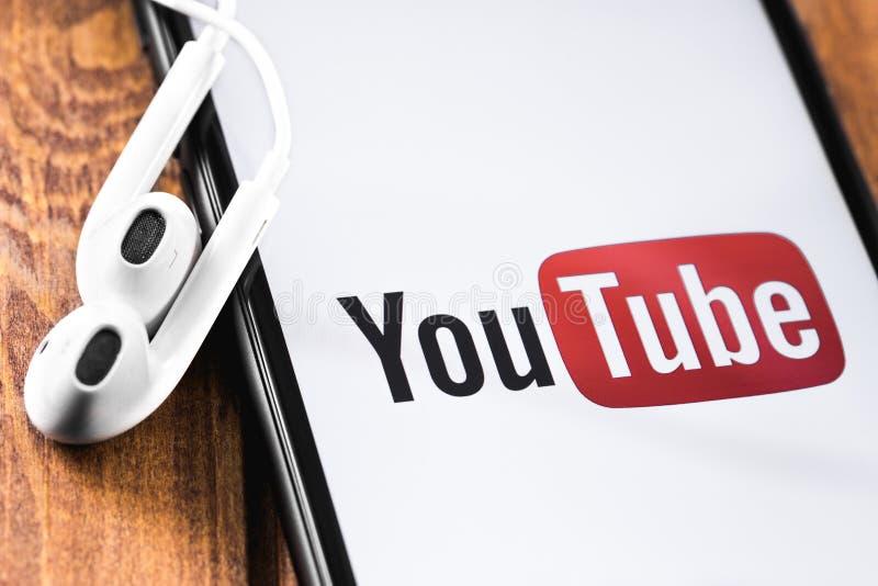 Logotipo de YouTube do close up no iPhone de Apple da tela com o Earpods no fundo de madeira YouTube ? uma aplica??o de partilha  imagens de stock royalty free