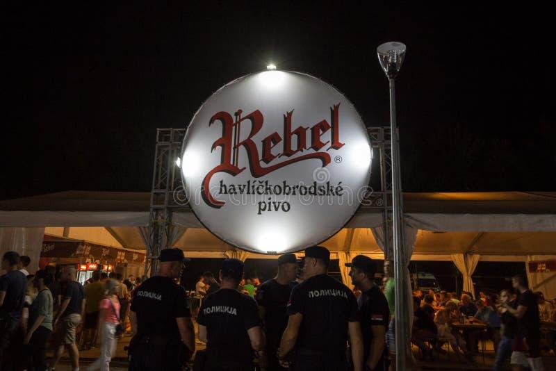Logotipo gigante de la cerveza rebelde de Pivo en una barra al aire libre del verano con los policías que se colocan en frente Pi fotos de archivo libres de regalías