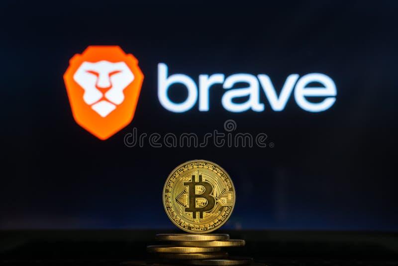Logotipo valiente en una pantalla de ordenador con una pila de monedas del cryptocurency de Bitcoin imágenes de archivo libres de regalías