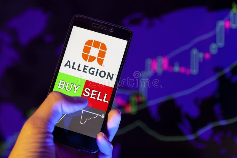 Logotyp ALLEGION PUBLIC LIMITED COMPANY på smartphone screen, hand till återförsäljare med mobiltelefon som visar KÖP eller SELL  arkivbilder