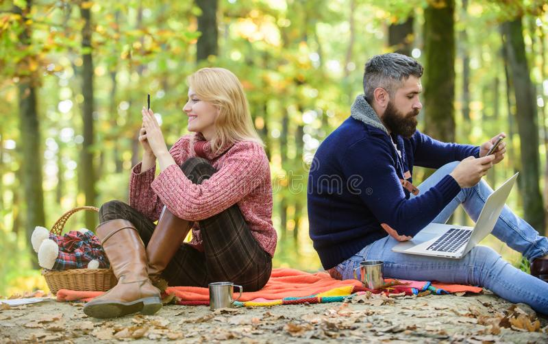 Logout of all accounts. Modern life. Happy loving couple relaxing in park with mobile gadgets. Modern people always. Involved online communication. Internet stock photo