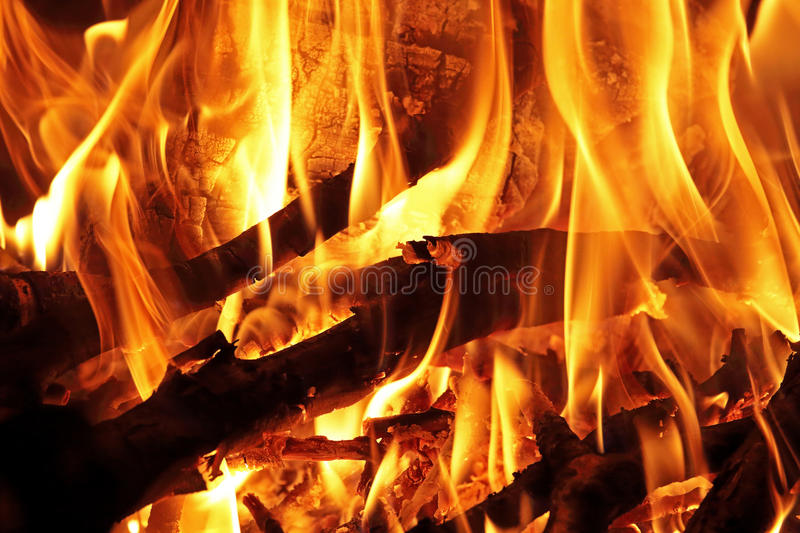 Logs and branches burning in a wood fire. Closeup flames of a wood fire with burning logs and branches stock images