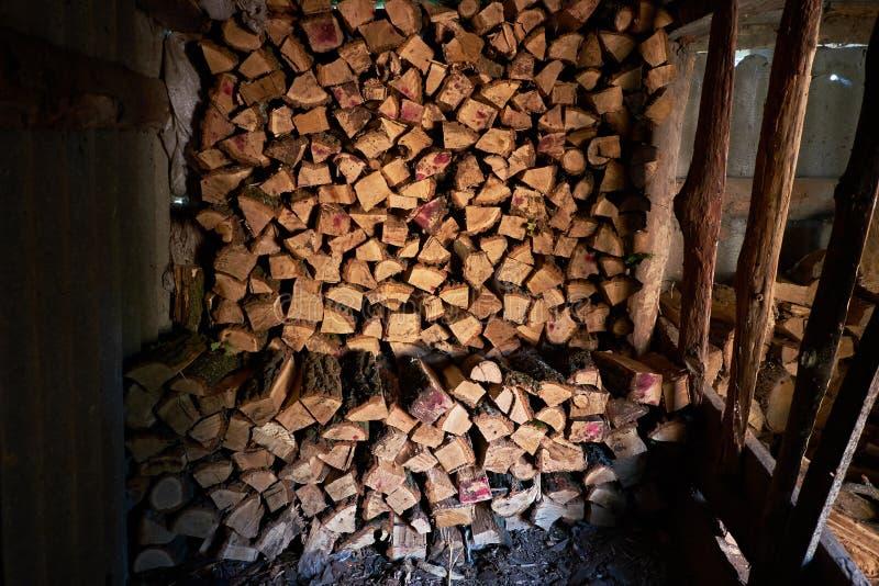 Logs de bois de chauffage entassés sous le toit d'ardoise. Carburant pour chauffage des poêles. Vie du pays. Mur empilé de bois photographie stock