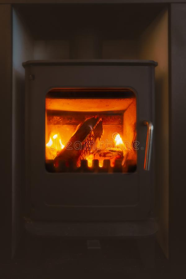 Logs durning on a cast iron glass fronted stove.  stock photography