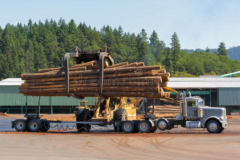 Logs Unloading Off Truck in Lumber Yard. Logs unloading off semi truck at lumber yard in Oregon royalty free stock photo