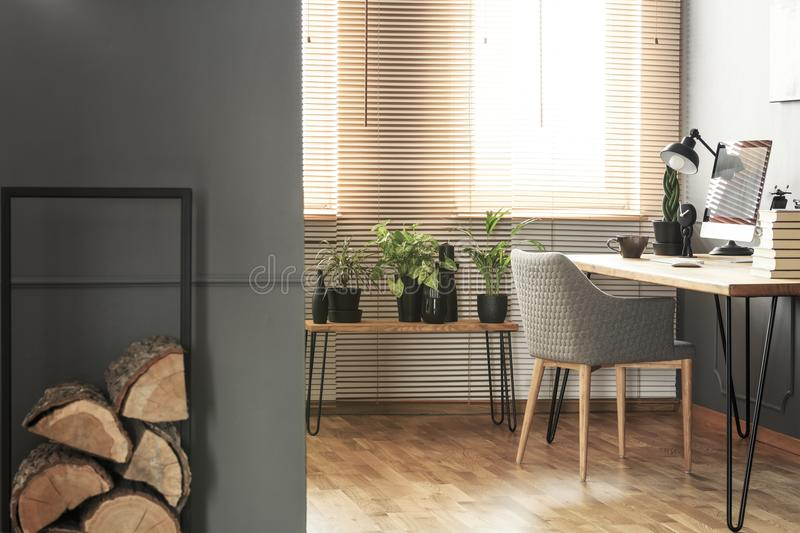 Logs of wood and plants in bright home office interior with grey. Armchair at desk. Real photo stock photo