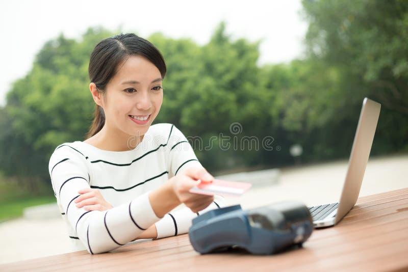 Lohn der jungen Frau auf Positions-Anschluss mit Kreditkarte stockfotografie