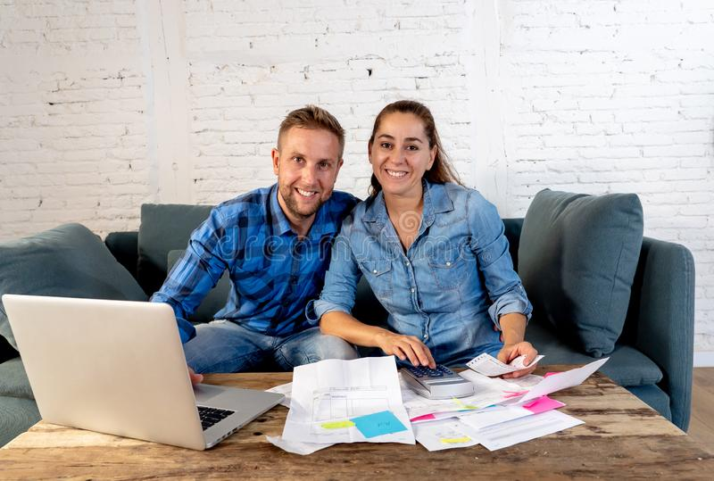 Lohnlisten der jungen glücklichen jungen Paare mit dem Laptop, der glücklich und weg von den Schulden glücklich sich fühlt lizenzfreies stockfoto