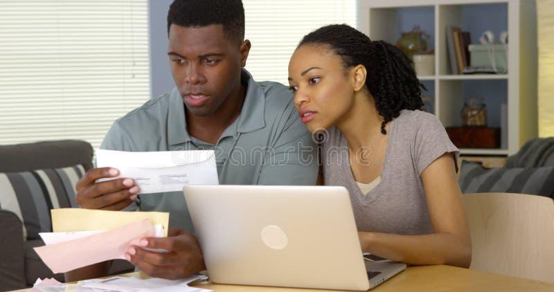 Lohnlisten der jungen schwarzen Paare online mit Laptop-Computer stockfotografie