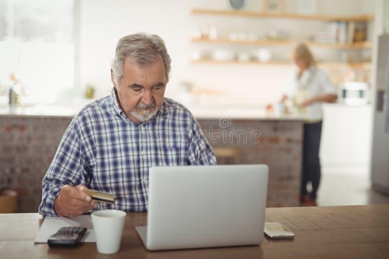 Lohnlisten des älteren Mannes online auf Laptop in der Küche stockbilder