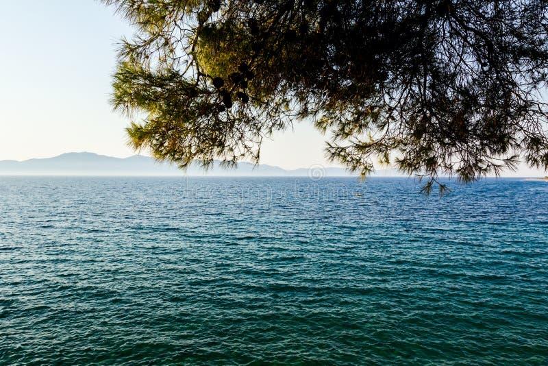 Loin îles comme silhouette à travers le bord de la mer image stock