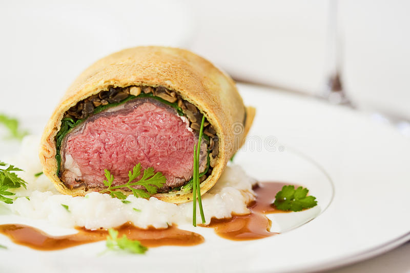 Loin of Lamb. Boneless Loin of Lamb wrapped in Pastry with Spinach, Mushrooms and Risotto royalty free stock image