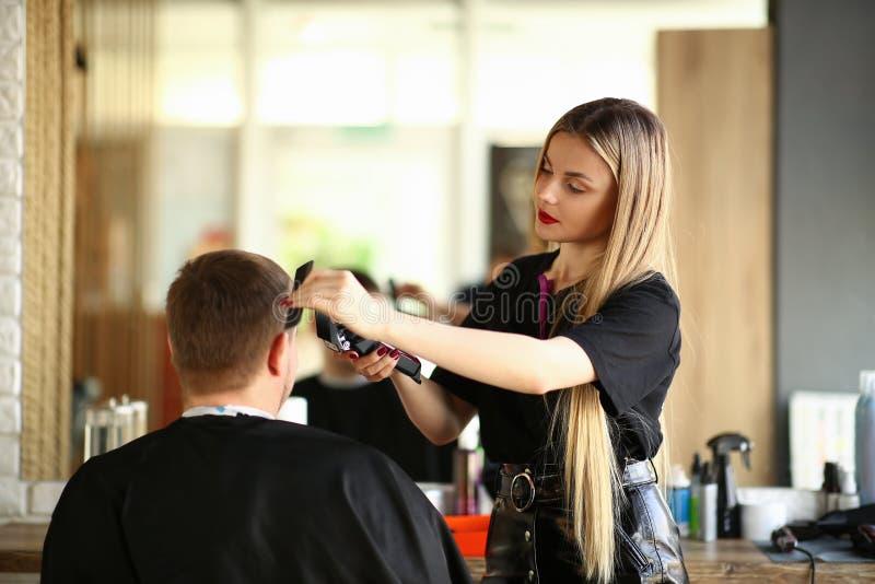 Loira Hairdresser Stendo Man por Electric Razor imagem de stock
