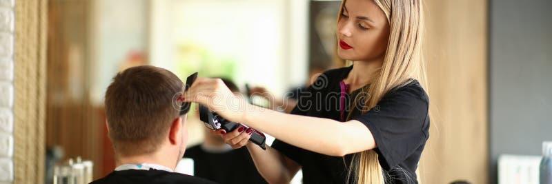 Loira Hairdresser Stendo Man por Electric Razor imagem de stock royalty free