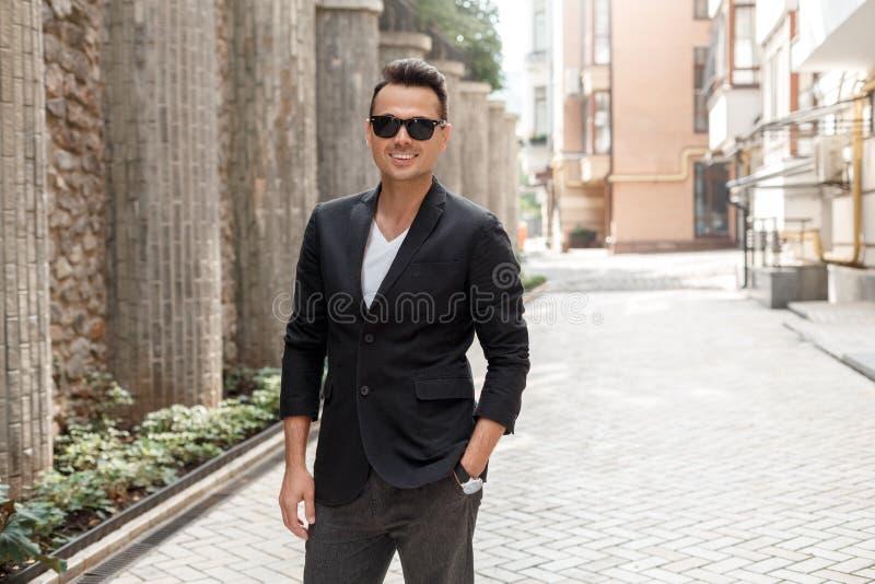 Loisirs d'extérieur Jeune homme dans le costume et lunettes de soleil se tenant sur le sourire de rue de ville gai photos libres de droits