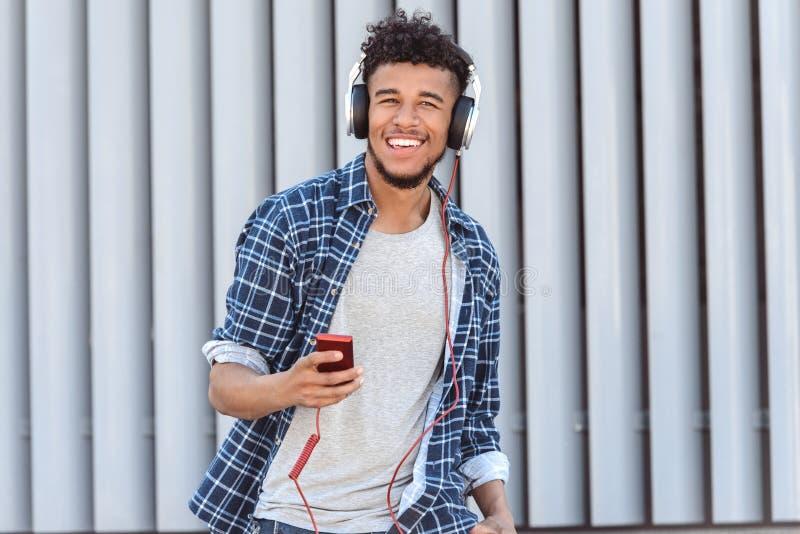 Loisirs d'extérieur Type de mulâtre dans des écouteurs se tenant sur la musique de écoute de rue de ville sur le sourire de joueu images libres de droits