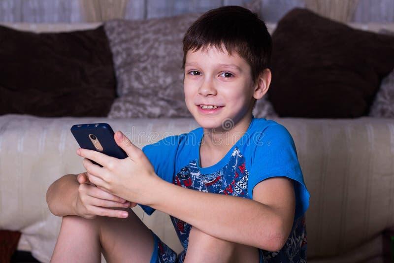 loisirs, enfants, technologie, communication d'Internet et concept de personnes - garçon de sourire avec le message textuel ou le photos stock
