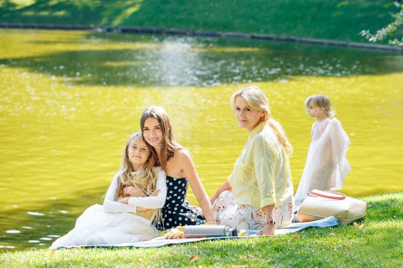 Loisirs, vacances et concept de personnes - famille féminine heureuse ayant le dîner ou la réception en plein air joyeux d'été images stock
