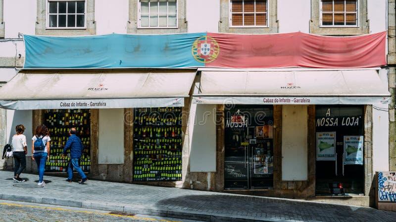 Loja antiga das bebidas famosas no centro de Porto, Portugal com a bandeira portuguesa drapejada fora foto de stock
