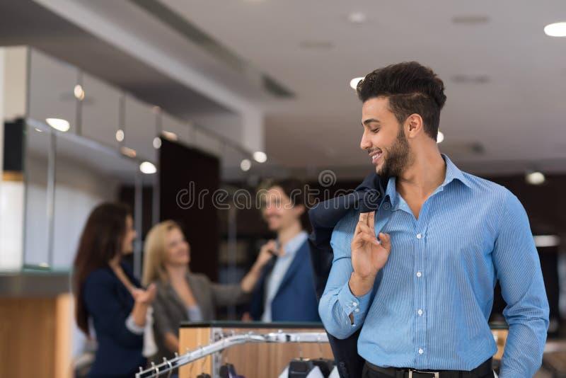 Loja considerável da forma do homem e da mulher de negócio, clientes que escolhem a roupa na loja foto de stock