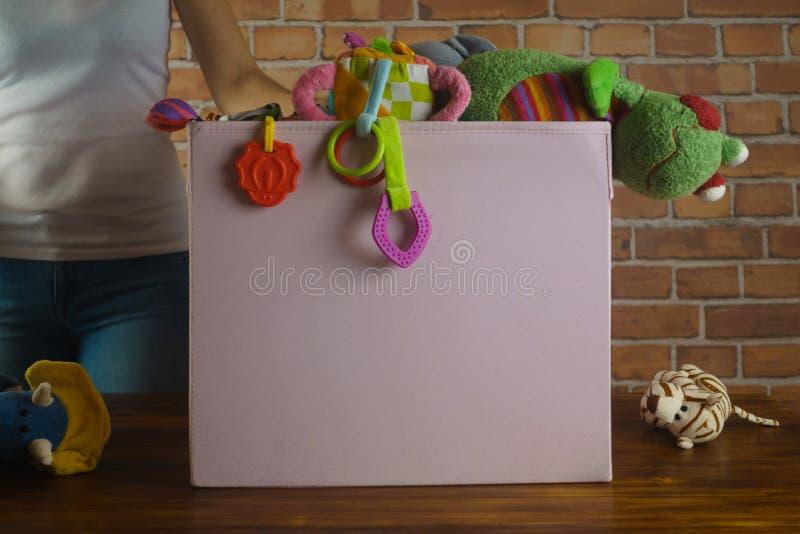 Loja da caridade Mulher que classifica os brinquedos usados que lhe doaram fotografia de stock