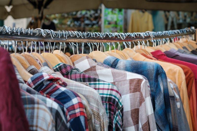 Loja da forma da segunda mão, close up das camisas que penduram em ganchos fotos de stock royalty free