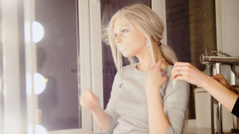 Loja de beleza: brincos louros adoráveis do desgaste do modelo da jovem mulher foto de stock