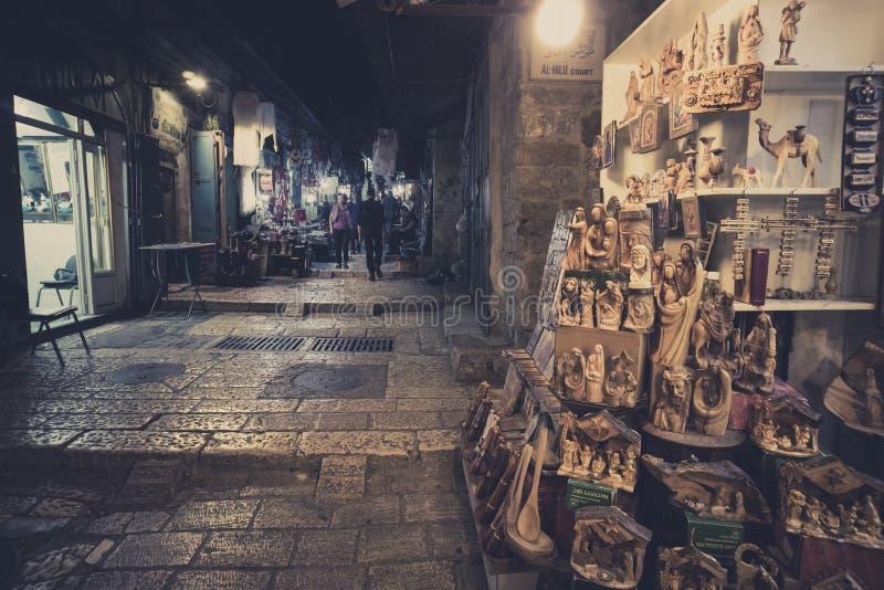 Loja de lembranças com as lembranças religiosas em alguma rua de compra do Jerusalém e em poucos turistas disparados na noite Jer fotografia de stock royalty free