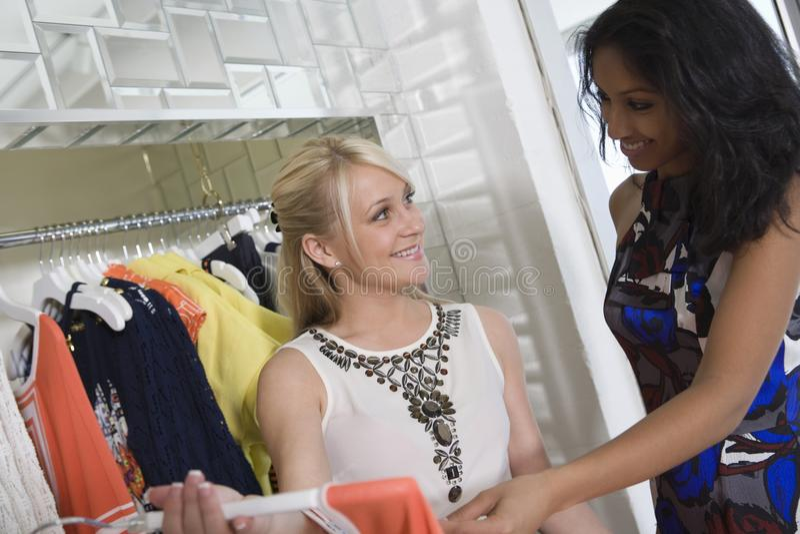 Loja de roupa de Helping Customer At do assistente de loja imagens de stock