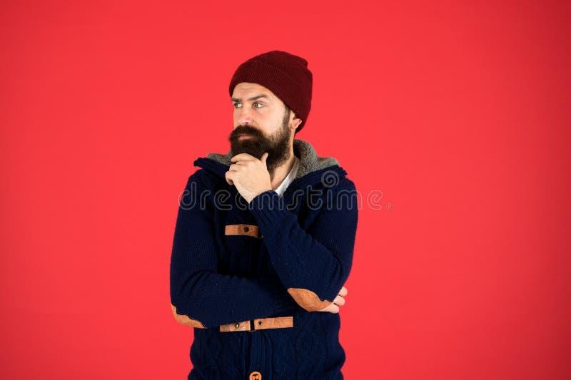 Loja de roupas de moda Conceito de roupas masculinas Pense e decida Maiôs de inverno Saltador quente barbudo e chapéu vermelho imagem de stock