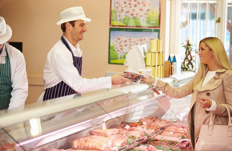 Loja de Serving Customer In do carniceiro fotografia de stock