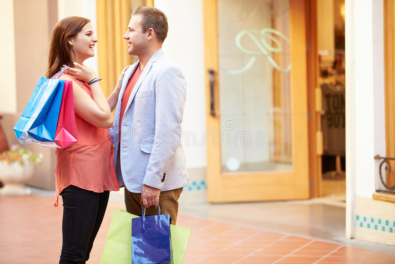Loja ereta da parte externa dos pares na alameda que guarda sacos de compras imagens de stock