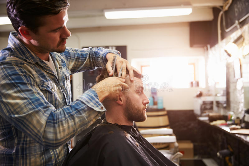 Loja masculina de Barber Giving Client Haircut In fotografia de stock