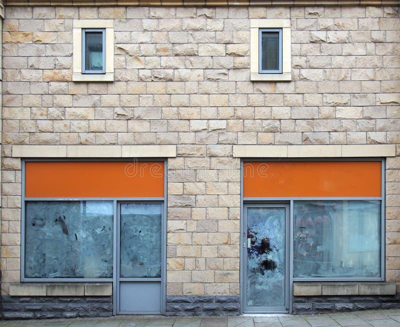 Lojas abandonadas vazias em uma rua com as janelas vazias whitewashed e sinais vazios da loja imagens de stock