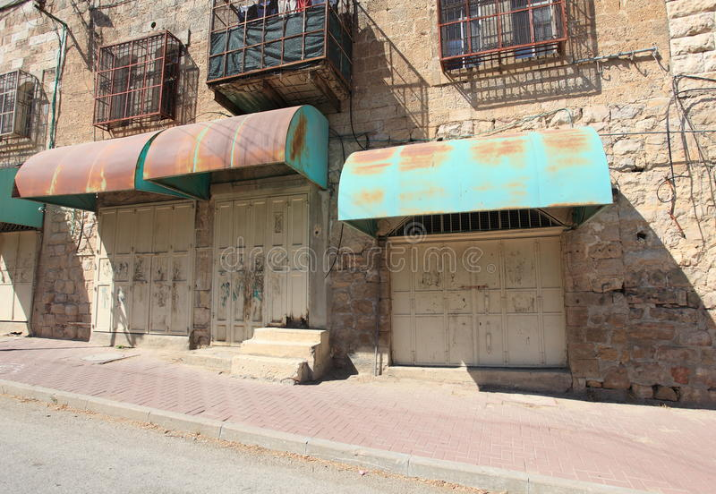 Lojas fechados, casas com raspagem, Hebron foto de stock