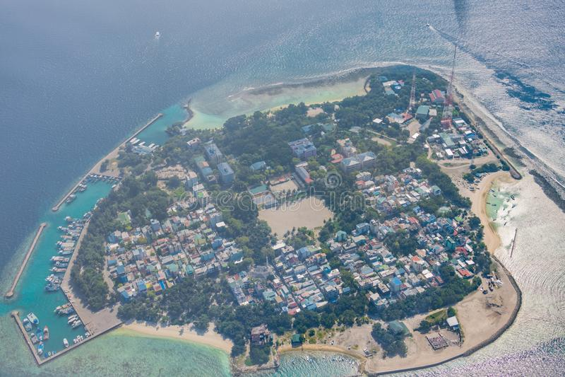 Lokaal het eilandsatellietbeeld van de Maldiven Huizen en haven met boten die met blauwe overzees omringen royalty-vrije stock foto's