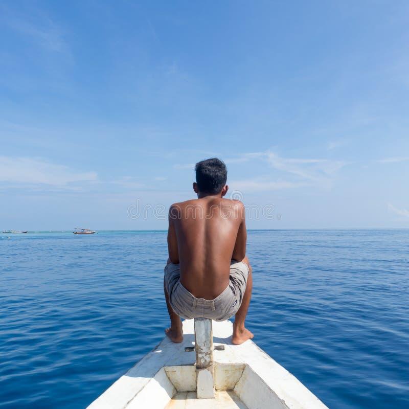 Lokaal Sportief Guy Sitting Topless bij de Boog die van Traditionele Witte Houten Zeilboot, Mooie Blauwe Overzees van Gili bekijk stock foto