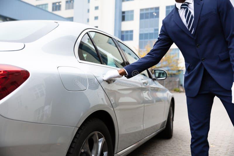 Lokaj r?ka Otwiera Samochodowego drzwi obraz royalty free