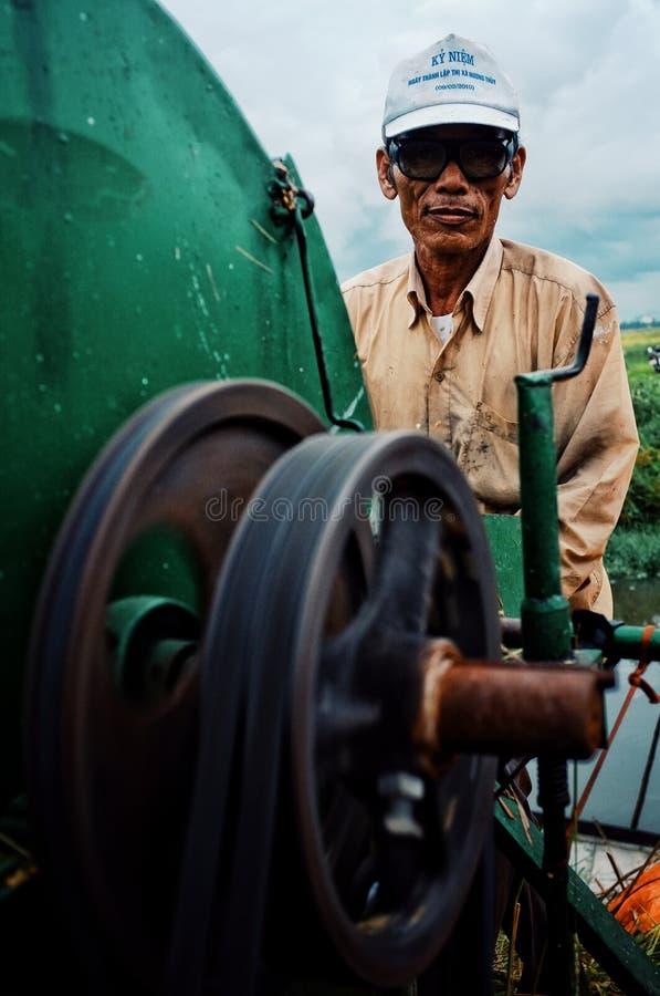 lokal bondeman som drar ut riskorn från växten med en mobil som tröskar - maskin bredvid en flod arkivfoton