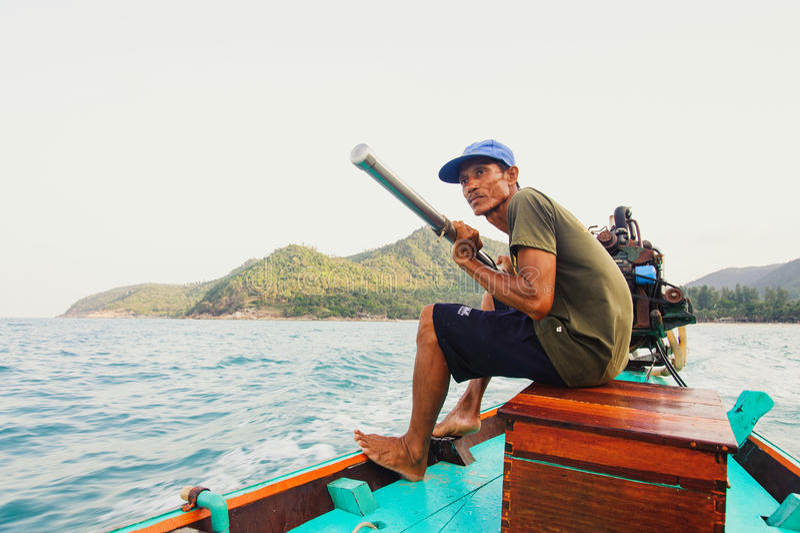 Lokal fiskare som styr hans typiska lång-svans fartyg med dieselmotorn arkivbilder