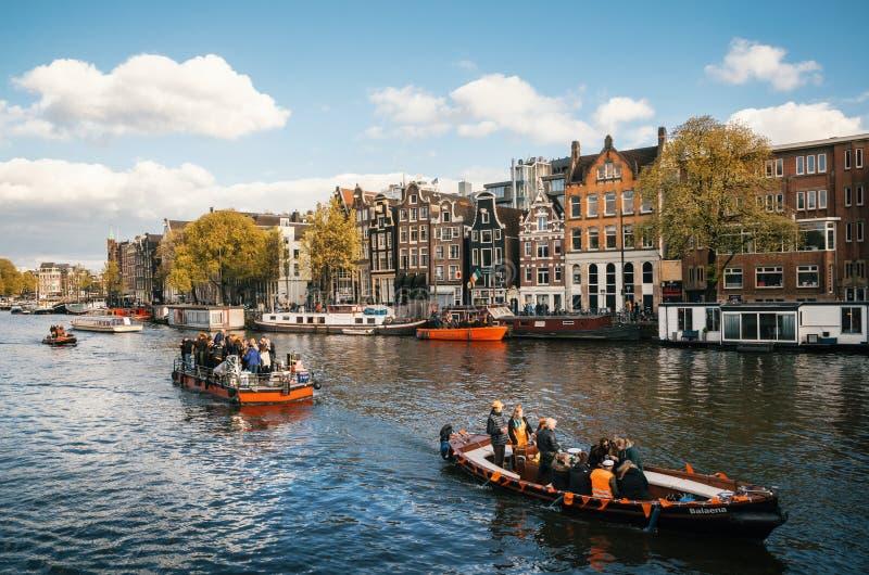 Lokal iklädd orange kläder för folk och för turister rider på fartyg och deltar, i att fira dag för konung` s arkivbilder