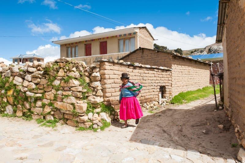 Lokal kvinna i nationella kl?der som g?r p? ?n av Sun Isla del Sol p? Titicaca sj?n, Bolivia arkivfoton