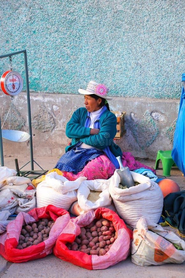 Lokal kvinna som säljer potatisar och korn på gatamarknaden i C arkivfoto