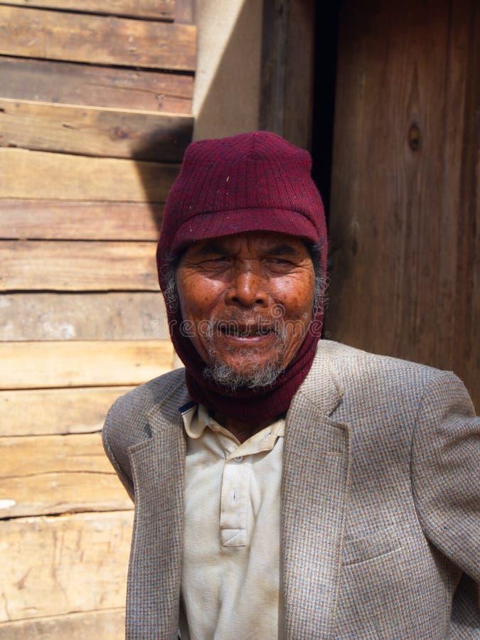 Lokal man i hus för skörd för kaffelantgårdby Lopp i Dalat arkivbilder