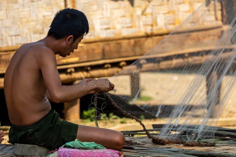 Lokal man som reparerar ett fisknät Laos royaltyfri bild